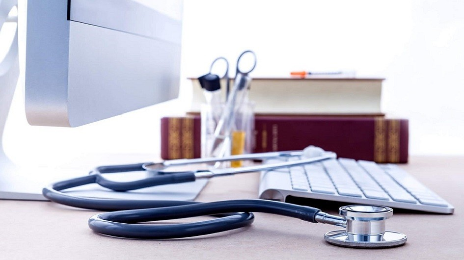 Stethoscope sitting on a desk next to a keyboard